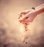 Песок моря понижается к земле через ладонь вашей руки Стоковая Фотография
