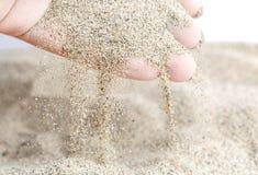 Песок полит от рук ` s женщин Макрос стоковые фотографии rf