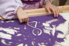 Песок притяжки девушек рук Стоковая Фотография RF