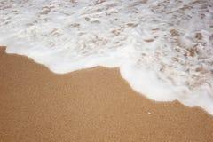 Песок пляжа и морская вода Стоковая Фотография