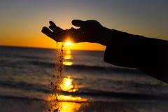 Песок смещая через пальцы Стоковые Изображения RF