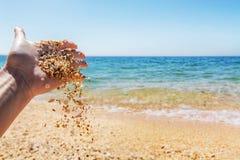 Песок Seashells scatter руки женщины на предпосылке моря стоковые фото