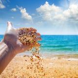 Песок Seashells scatter руки женщины на предпосылке моря, стоковые фото