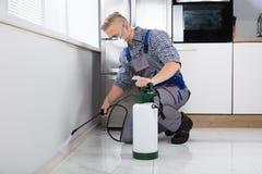 Пестицид работника распыляя на стене стоковая фотография rf