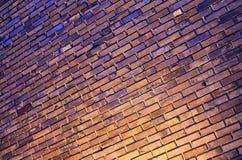 Пестротканая кирпичная стена с освещением на ноче, предпосылке, раскосном положении Стоковое Изображение