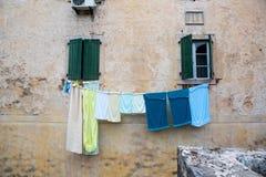 Пестротканое белье высушено вне окна старого дома стоковые фотографии rf