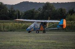 Пестротканое воздушное судно свет-двигателя с пропеллером от заднего подготовлено для взлета на травянистом авиаполе стоковое изображение rf