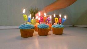 Пестротканое пирожное с свечами в честь вечеринки по случаю дня рождения Рука конца-вверх молодого человека освещает свечи на пир сток-видео