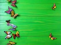 Пестротканые бабочки на зеленой деревянной предпосылке Стоковые Фото