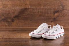 Пестротканые ботинки спортзала молодости на поле Стоковые Изображения