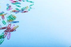 Пестротканые бумажные зажимы на голубой предпосылке, картине, космосе экземпляра стоковое изображение