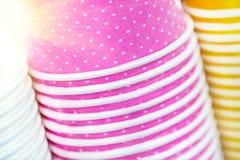 Пестротканые бумажные стаканчики Яркие еда и предпосылка питья Стог красочных контейнеров Закройте вверх по куче стекел стоковые фото