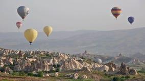 Пестротканые воздушные шары летают над утесами сток-видео