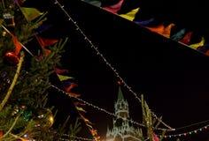 Пестротканые гирлянды флагов и электрические лампочки против фона башни Spassky Москвы Кремля стоковая фотография