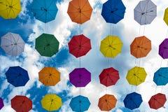 Пестротканые зонтики вися высоко над землей стоковые фотографии rf