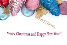 Пестротканые игрушки рождества на белой предпосылке Стоковая Фотография