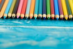 Пестротканые карандаши на деревянной предпосылке Много красивых multic стоковые изображения rf