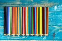 Пестротканые карандаши на деревянной предпосылке Много красивых multic стоковое фото