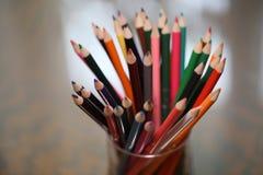 Пестротканые карандаши на таблице Стог покрашенного ti карандашей Стоковые Изображения