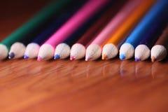 Пестротканые карандаши на таблице Стог покрашенного ti карандашей Стоковая Фотография