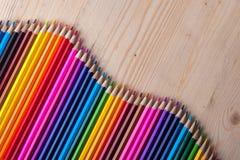 Пестротканые карандаши на деревянном столе, взгляд сверху стоковое изображение