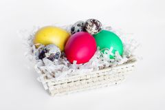 Пестротканые пасхальные яйца лежат в корзине на белой предпосылке Яйца желтых, красных, зеленых и триперсток i стоковое фото