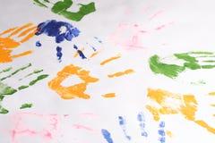 Пестротканые печати рук вышли с краской других цветов на белую бумагу, ладоней на бумаге Стоковые Фото
