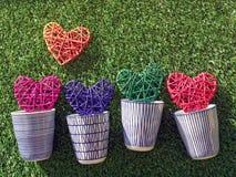 Пестротканые плетеные сердца в чашках фарфора на фоне зеленой травы Стоковая Фотография
