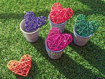 Пестротканые плетеные сердца в чашках фарфора на фоне зеленой травы Стоковое Изображение RF