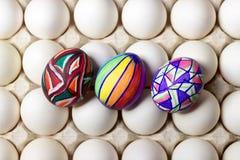 Пестротканые покрашенные пасхальные яйца дерева на белом подносе, фотографии еды Стоковое Фото