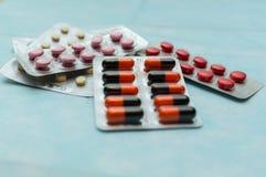 Пестротканые таблетки и капсулы в конце-вверх волдырей, на голубой предпосылке r Концепция обрабатывать человеческие заболевания стоковая фотография rf