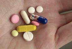 Пестротканые таблетки на руке Стоковая Фотография
