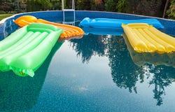 Пестротканые тюфяки воздуха плавая на спокойную поверхность более малого бассейна Стоковая Фотография