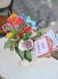 Пестротканые украшения букета и бумаги свежих цветков в вазе на таблице и бирке с словами все еще определяют венчание таблицы сте Стоковые Изображения