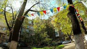Пестротканые флаги отбрасывают ветер между деревьями акции видеоматериалы