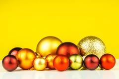 Пестротканые шарики рождества на желтой предпосылке Стоковые Фото