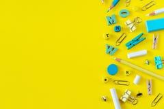 Пестротканые школьные принадлежности на желтой предпосылке с космосом экземпляра стоковые изображения