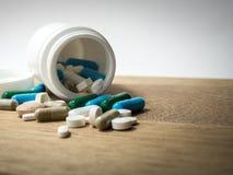 Пестротканый лекарства и капсулы на деревянном столе closeup Мы против лекарств лекарств анти-, лечения в контейнере для здоровья Стоковые Фотографии RF