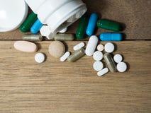 Пестротканый лекарства и капсулы на деревянном столе closeup Мы против лекарств лекарств анти-, лечения в контейнере для здоровья Стоковые Изображения