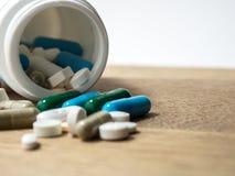 Пестротканый лекарства и капсулы на деревянном столе closeup Мы против лекарств лекарств анти-, лечения в контейнере для здоровья Стоковая Фотография RF