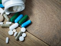 Пестротканый лекарства и капсулы на деревянном столе closeup Мы против лекарств лекарств анти-, лечения в контейнере для здоровья Стоковое фото RF