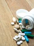 Пестротканый лекарства и капсулы на деревянном столе closeup Мы против лекарств лекарств анти-, лечения в контейнере для здоровья Стоковые Фото