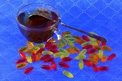 Пестротканый мармелад и чашка черного чая Стоковые Фото