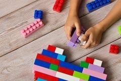 Пестротканый пластиковый конструктор в руках девушки Игры ` s детей воспитательные стоковая фотография