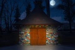 Пестротканый покрашенный маленький дом вечером с полнолунием Красочный каменный дом как в сказки стоковые изображения