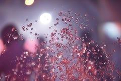 Пестротканый фонтан брызга на ноче стоковая фотография rf