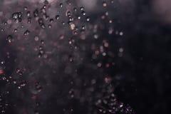 Пестротканый фонтан брызга на ноче стоковые фотографии rf