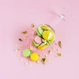 Пестротканый macaroon в вине на розовой предпосылке Author& x27; s обрабатывая, космос для текста Стоковые Изображения RF