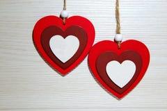2 пестротканых деревянных сердца на светлой предпосылке Символ  Стоковое Фото