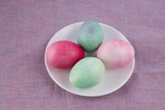4 пестротканых покрашенных пасхального яйца на белых плите и сирени Стоковое фото RF